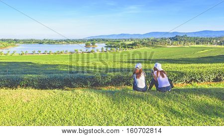 Two girls with smartphone relaxing in the tea plantation with lake blue sky background