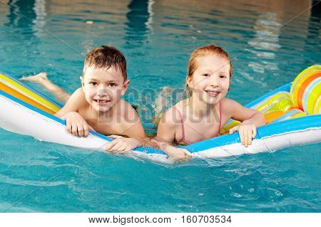 Little girl and boy floating on pool raft in pool