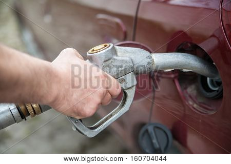close-up of a hand pumping gas in the car with a gas pump