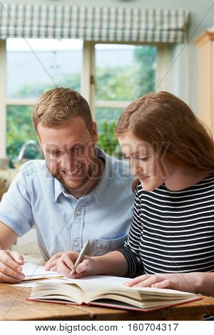 Male Home Tutor Helping Teenage Girl With Studies