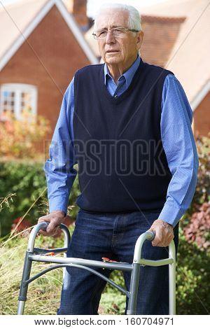 Depressed Senior Man Using Walking Frame Outdoors