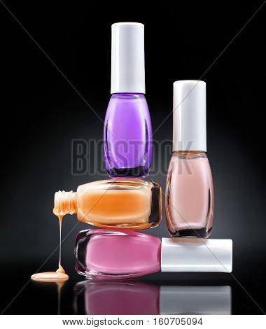 Nail polish dripping from stacked bottles on dark background. Close up.