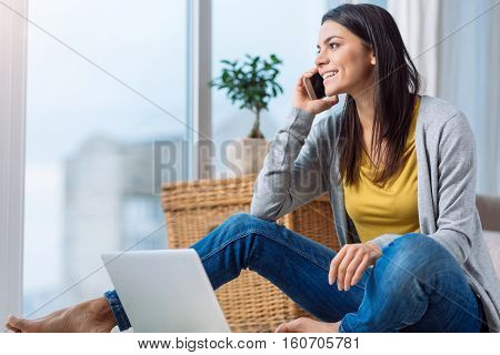 Involved in the conversation over the phone. Delighted happy cheerful woman sitting on the floor in front of the laptop while speaking over the phone and expressing happiness