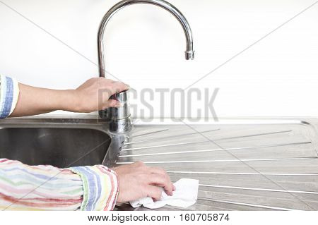 Houseproud woman cleaning a stainless steel sink in her kitchen with a disposable tissue selective focus closeup