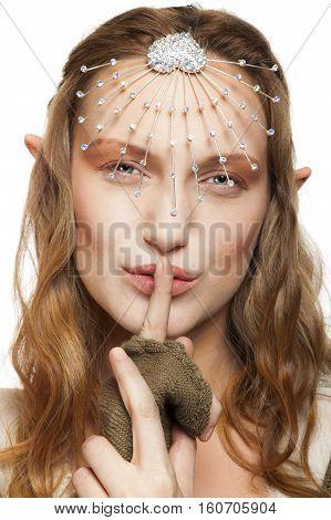 Beautiful elf woman, looking at camera and making a shush sign.