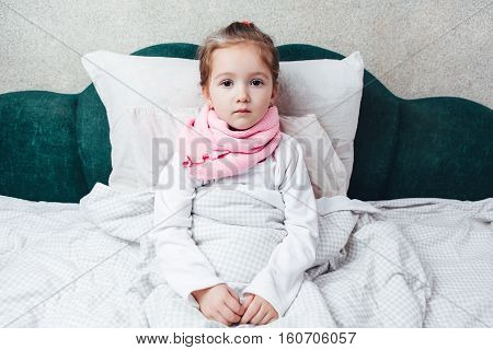 Cute sick little girl lying in the bed in pink scarf