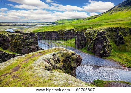 Bizarre shape of cliffs surround the stream with glacial water. The striking canyon in Iceland. The concept of active northern tourism