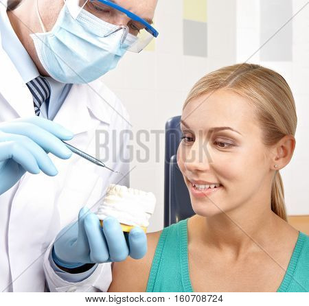 Dentist showing female patient artificial model of teeth