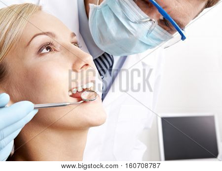 Dentist holding dental instruments in young woman's mouth