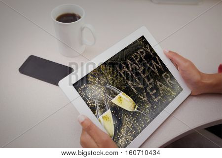 Woman using tablet pc against champagne flutes clinking against glittering happy new year