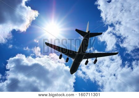 Airplane in clouds deep blue sky. Airplane travel composition. Airplane silhouette in sky.