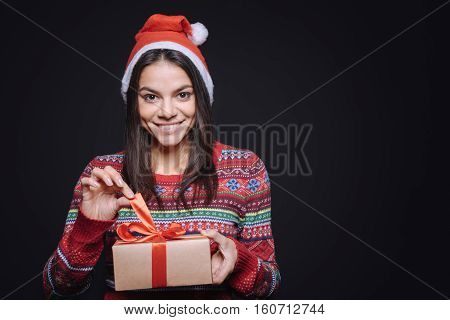 Full of delight. Cheerful happy smiling girl standing isolated in black background while expressing joy and unpacking the box with a gift