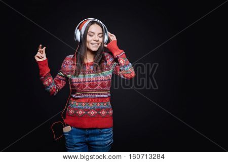 Peaceful tune. Smiling inspired involved girl standing against the black background while expressing peacefulness and listening to the music in the earphones