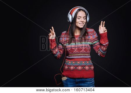 Time for a melodic meditation. Smiling inspired involved girl standing against the black background and expressing peacefulness while listening to the music in the earphones and dancing