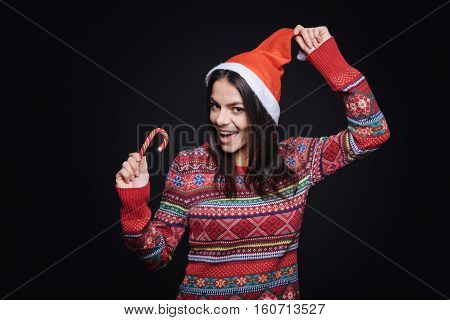 Happy from coming holidays. Surprised amused joyful girl standing isolated in black background and expressing joy while eating the candy stick