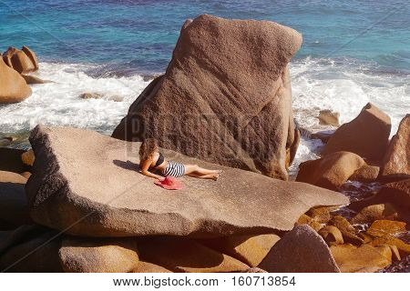 Female  in a red hat in the pool against the backdrop of mountains and ocean