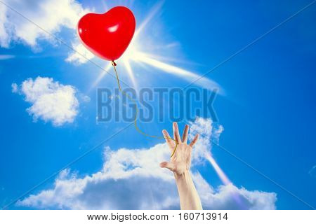 The hand tries to catch a departing balloon in the form of heart against the solar sky.