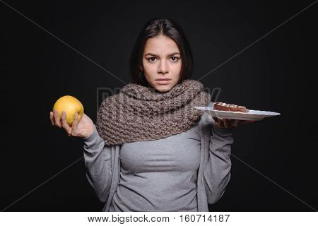 Hard choice. Puzzled upset doubtful woman holding a plate with a piece of cake and an apple while standing isolated in black background and trying to make a decision