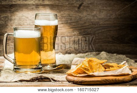 Beer in mug, glass on wooden table with wheat spikelets and potato chips on board