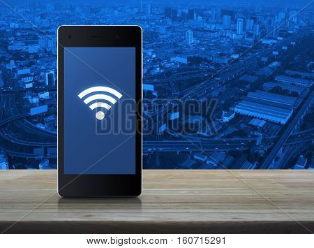 Wi-fi connection icon on modern smart phone screen on wooden table over aerial view of cityscape expressway and highway Technology and internet concept
