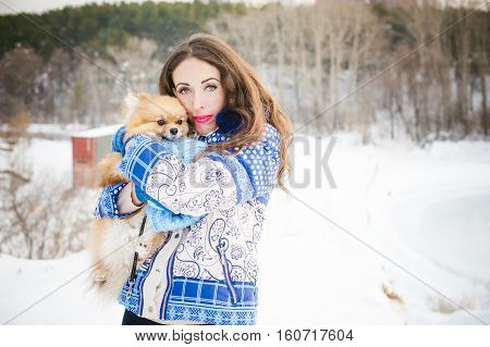 Smiling Woman Holding Her Pet Dog In His Hands Near Face, Hugging. Spitz Breed Dog Playing With A Wo