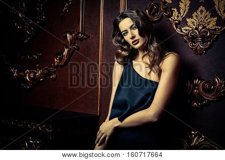 Beautiful sensual woman wearing black evening dress standing by a fireplace in luxurious apartments. Glamorous woman. Vintage style.