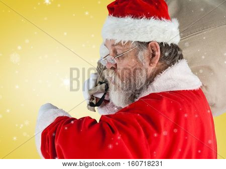 Santa checking the time against digitally generated yellow background