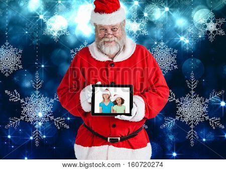 Santa claus holding a digital tablet with photo of christmas kids against digitally generated christmas background