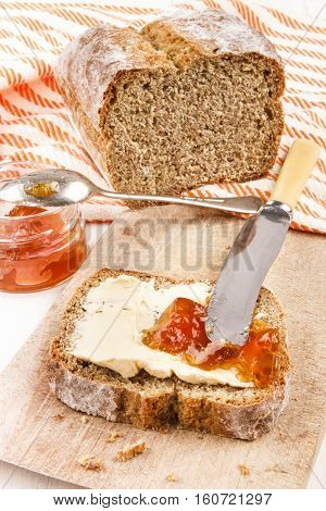home baked irish soda bread with butter and orange jam on a wooden board