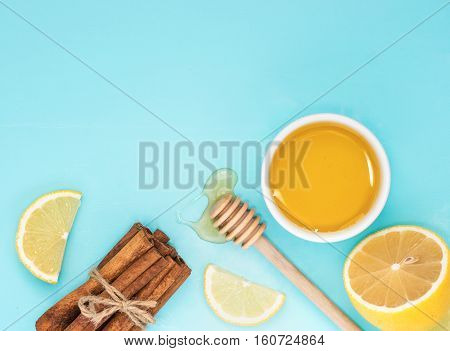 Lemon, Cinnamon Sticks And Honey On Blue With Copy Space