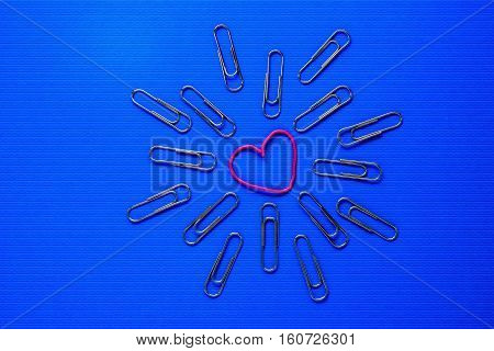 paperclip on a blue background in the center of the pink clip in the shape of a heart
