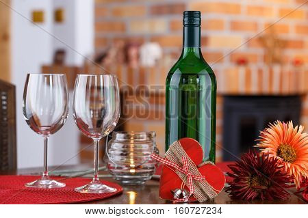 Still life with wine bottles glasses flowers and heart symbol on the background a brick fireplace