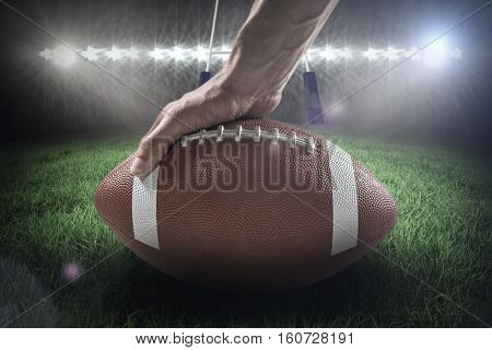 American football player holding ball against rugby pitch 3D