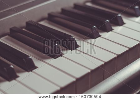 Piano keyboard black and white keys close-up musical instrument retro toning selective focus