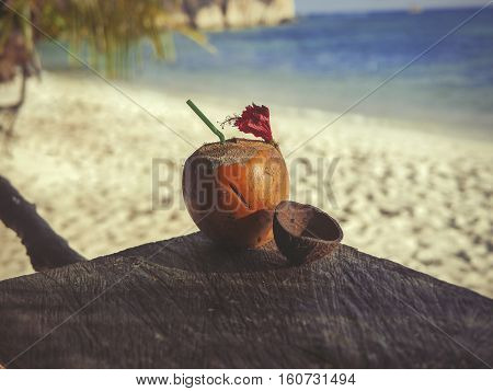 Seychelles coconut with a straw on a table in front of the ocean