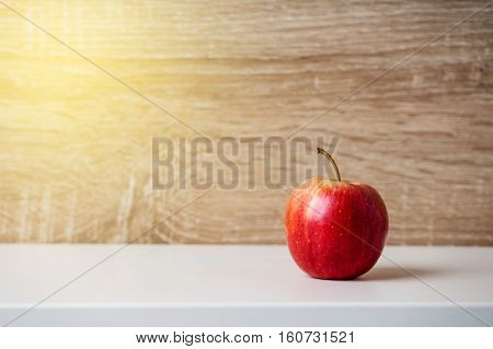 Fresh ripe red apple on wooden background