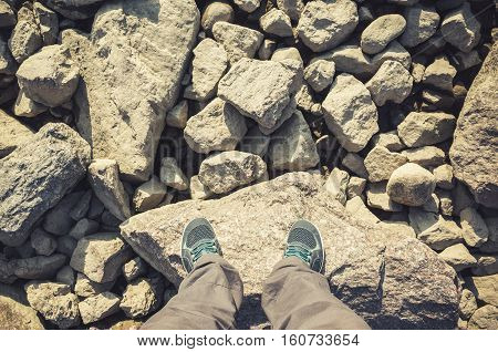 Male Feet In Canvas Shoes Stand On Rocks
