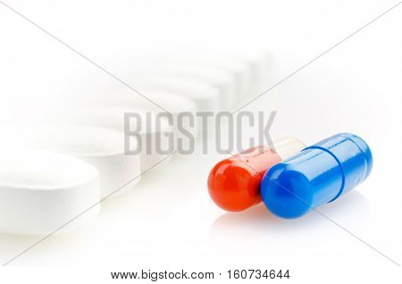 Red and Blue Capsules on a Background of White Pills. Closeup.