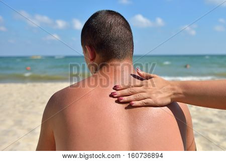 Hand Of A Woman Applying Sun Cream On A Male Back With Sunscreen Before Sunbathing At The Beach. Sun
