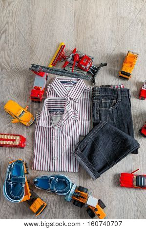 Boy Outfit Near Car Toy. Striped Shirt, Denim Pants And Blue Boat Shoes  Yellow  Red Cars. Top View.