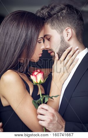 Young man give rose to lover indoor couple in love whispering confession