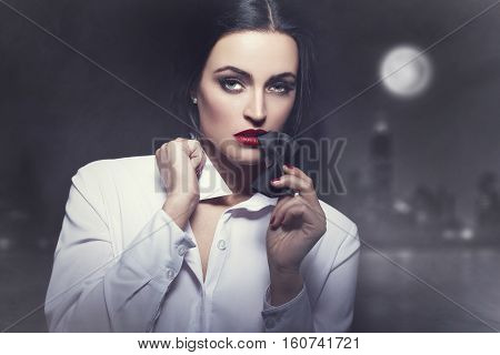 Sexy woman bite tux at night city sensuality and desire
