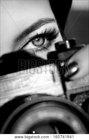 Pretty girl with beautiful eyes make pictures in a city park. Black and white photo.