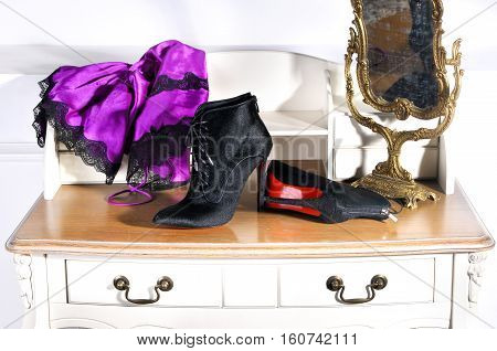 Ukraine Kiev - August 25 2016: Women's black ankle boots handmade. Imitation brand shoes Christian Louboutin showing red soles - illustrative editorial. female boudoir (dressing table and mirror)