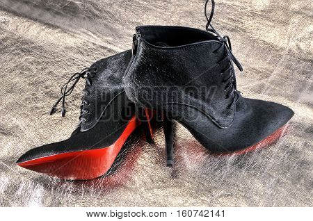 Ukraine Kiev - August 25 2016: Women's boots handmade on a piece of material from the golden skin. Imitation brand shoes Christian Louboutin showing red soles - illustrative editorial