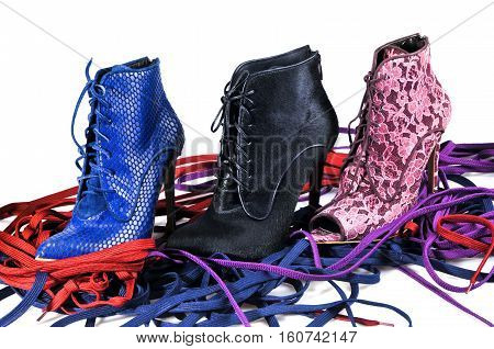Sexy women's shoes on a background of colored laces. Bright blue burgundy lace and black fur ankle boots. Footwear of three different colors and materials.