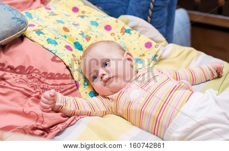 Baby wakes up and stretches in bed
