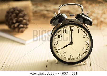 Clock displays the time eight o'clock,Clock on a wooden table with natural light