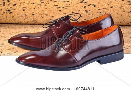 Men's classic leather shoes designed with a slim elongated toe made from a smooth brown leather. standing on a sheet of balsa wood