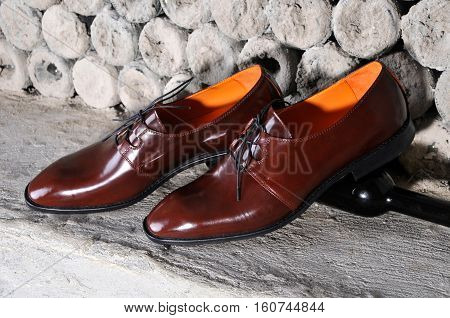 Classic shiny brown mens shoes standing on bottles